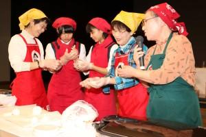 地元高校生とともに「焼きもち」の調理方法を実演するJA女性部員